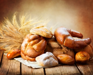 Bakery Bread on a Wooden Table. Various Bread and Sheaf of Wheat